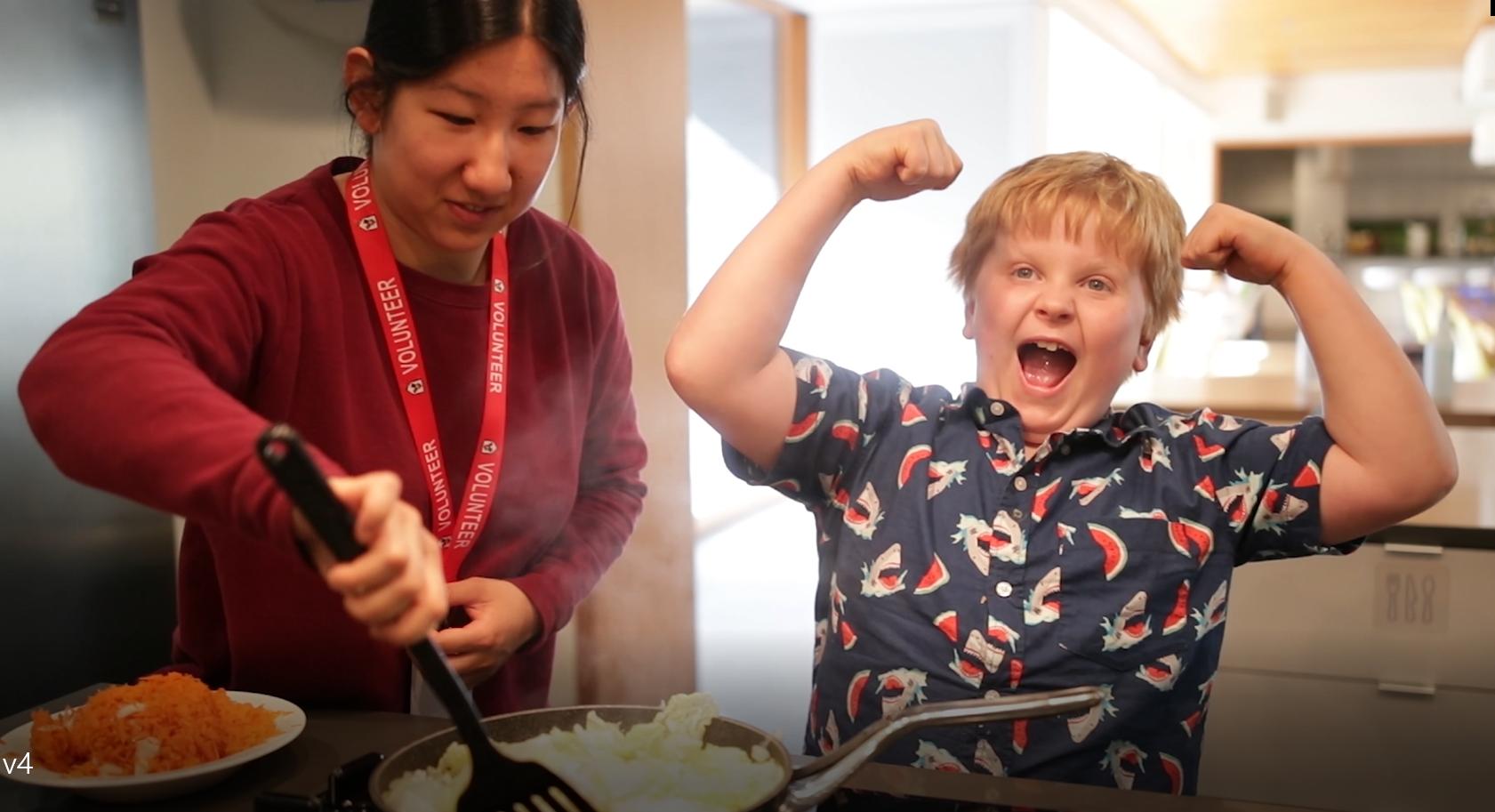 Volunteer and kid cooking